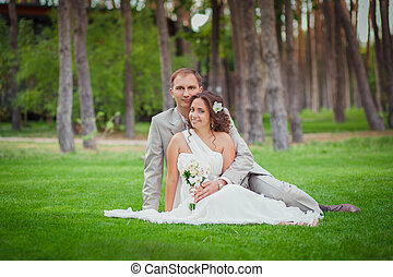 groom and bride sitting on the lawn