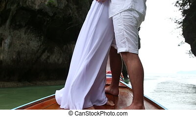 groom and bride stand on longtail boat in sea near cliff