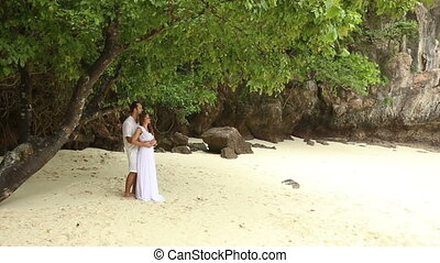 groom and bride standing on white sand beach
