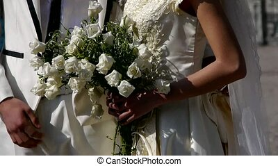 Groom and bride together, Bride carrying a bouquet of ...