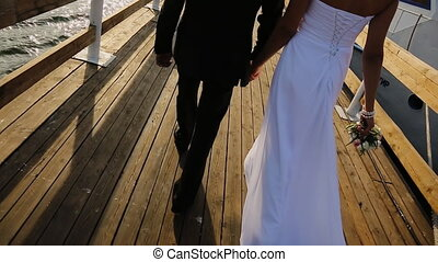 Groom and bride together go on the pier to his boat. Hands of the bride's beautiful and delicate bouquet of delicate flowers, and her long white dress. Wedding couple.