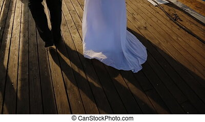Groom and bride together go on the pier to his boat. Her long white dress. Hands of the bride's beautiful and delicate bouquet of delicate flowers, and they are Wedding couple.
