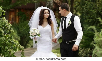 Groom and bride walking on park