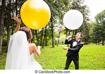 groom and bride with balloons outdoors