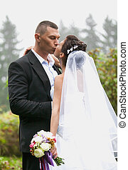 Groom and bride with long veil kissing at park