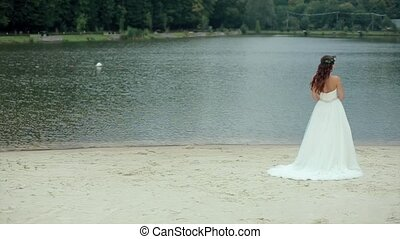 Groom Approaches Bride on Back of Background Lake