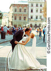 Groom bends bride over kissing her on a city square