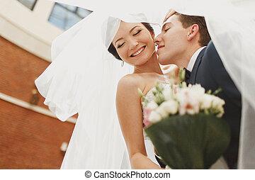 Groom bend's bride over kissing her under a veil