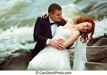 Groom bends bride over sitting on the stones behind a mountain river