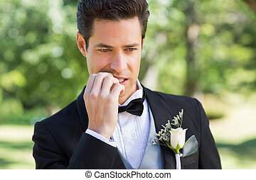Groom biting nails in garden
