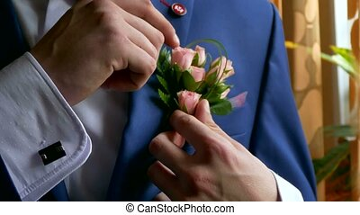 groom boutonniere on a man corrects his pocket hand