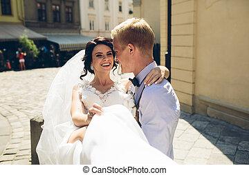 groom carries bride in his arms