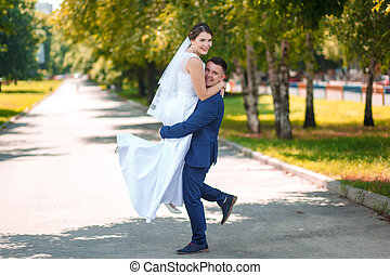 groom carries his bride in arms