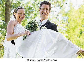 Groom carrying bride in garden - Happy groom carrying bride...