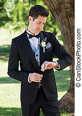 Groom checking time in garden