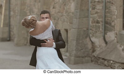 Groom circling bride close to the walls of castle