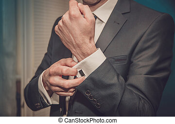 groom clasps cuff links on a shirt sleeve close up
