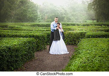 Groom covering bride with jacket at garden