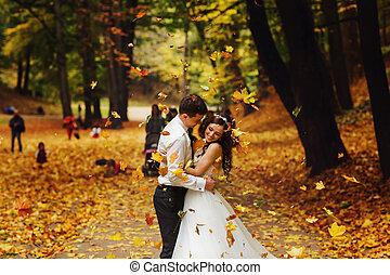 Groom embraces a bride under the shower of golden leaves
