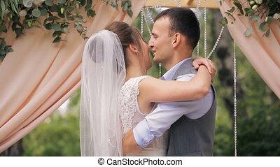 Groom embraces and kisses beloved after wedding ceremony.