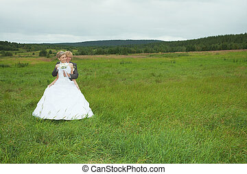 Groom embraces the favorite bride in field