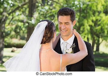 Groom embracing woman in garden