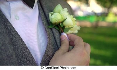 Groom fixing boutonniere by his hand