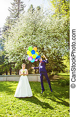 Groom flies on the balloons, but the bride holds his hand. Funny wedding. Groom jumps and flies on balloons. Young husband flying from his wife. Funny wedding concept. Happy Valentines day