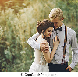 groom gently embracing his bride in the forest