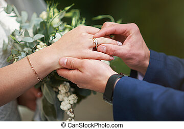 groom hand putting a wedding ring on the bride finger