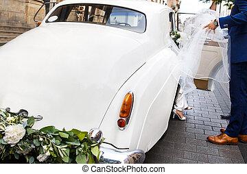 Groom helping the bride. Retro white car