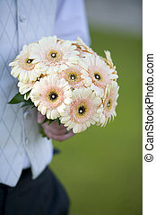 groom holdin a wedding bouquet