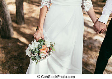 groom holding a bride hand with weding bouquet on wedding day