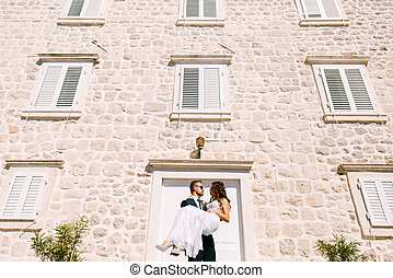 Groom holding bride in his arms against the stone wall of the building on a bright sunny day.