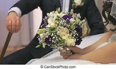 Groom holding cane sits next to bride. Close-up