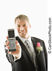 Groom holding cellphone.