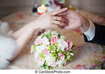 Groom holding hands of bride with wedding ring in restaurant