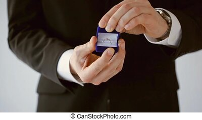 groom holding wedding ring - groom or salesman holding a box...