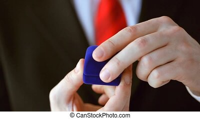 groom holding wedding ring