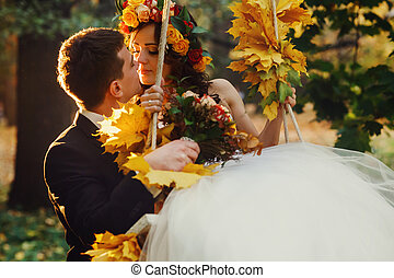 Groom holds a bride in a swing decorated with yellow fallen leaves
