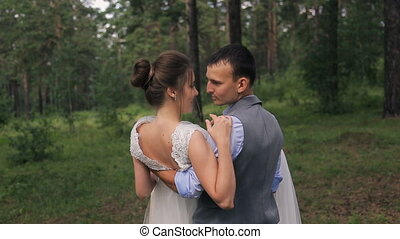 Groom holds bride on arms on photoshoot in forest outdoors