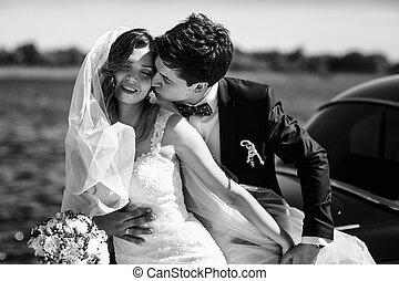 Groom holds bride tender kissing her neck behind an old car