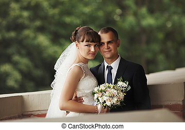 Groom holds bride's waist delicately standing on the brick balcony