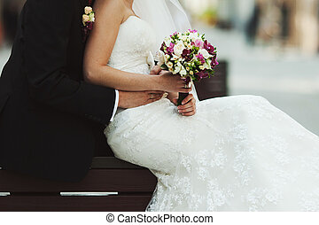 Groom holds delicate bride waist while she lies her hands with a bouquet on the skirt