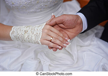 groom holds his bride's hand with wedding ring