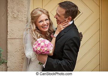 Groom holds in his arms a smiling bride