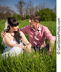 groom hugging bride on big field at sunny day