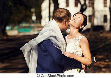 Groom hugs a bride being hidden under a veil