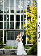Groom hugs a bride from behind standing in the front of glass building