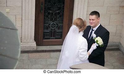 groom hugs and kiss his bride